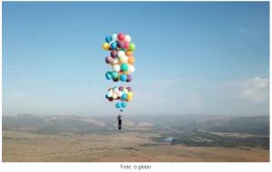 homem voa em cadeira por balões de hélio